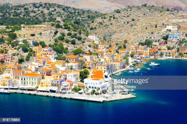 view over harbour to colourful houses, symi, dodecanese islands, south aegean, greece - symi foto e immagini stock
