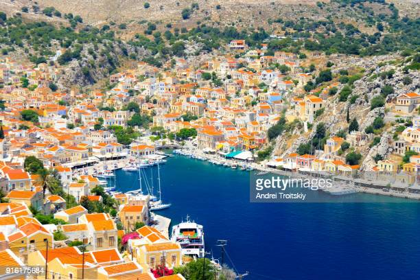 view over harbour to colourful houses, symi, dodecanese islands, south aegean, greece - symi stock photos and pictures