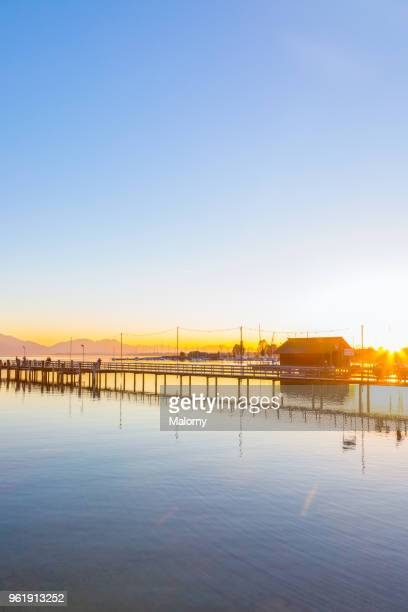 View over Lake Chiemsee with landing stage at sunset with mountain range in the background. Chiemgau, Bavaria, Germany