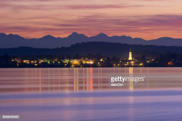 View over Lake Starnberg to illuminated town Seeshaupt, Bavarian and Austrian Alps in background, Upper Bavaria, Germany