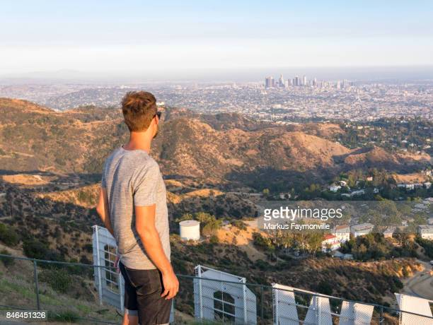 view over los angeles skyline with man in front of hollywood sign - hollywood hills stock photos and pictures