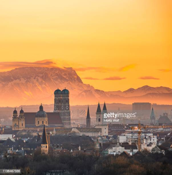 view over munich with church of our lady, theatine church, ludwigskirche, behind zugspitze at sunset, munich, bavaria, germany - munich photos et images de collection