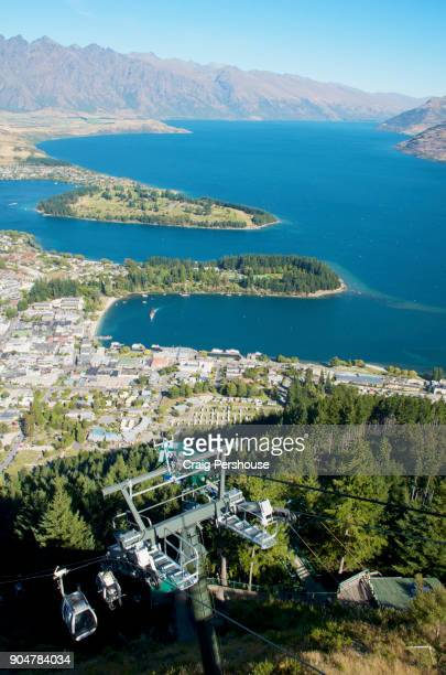 View over Queenstown and Lake Wakatipu from Bob's Peak, with Skyline Gondola cable cars approaching and leaving.