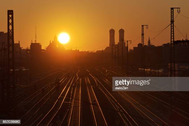 View over railroad tracks leading to Munich Central Station with Munich Cathedral Frauenkirche, taken at sunrise, Munich, Bavaria, Germany