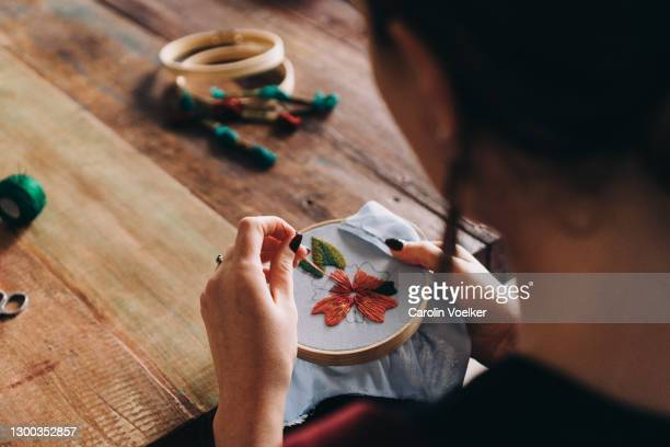 view over shoulder of a woman doing embroidery and colourful needlework - needlecraft stock pictures, royalty-free photos & images