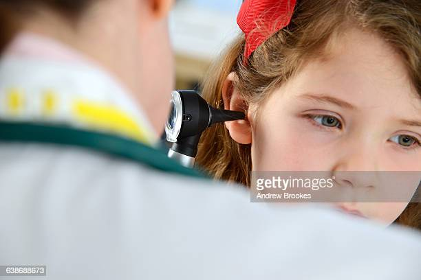 View over shoulder of doctor conducting otoscopy examination on girl