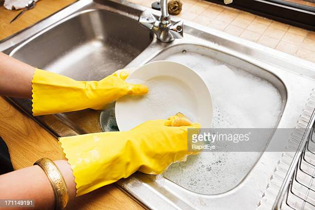 view over shoulder of young woman doing the dishes - dishwashing liquid stock photos and pictures