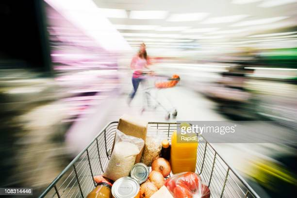 View over supermarket shopping cart and shopper with motion blur.