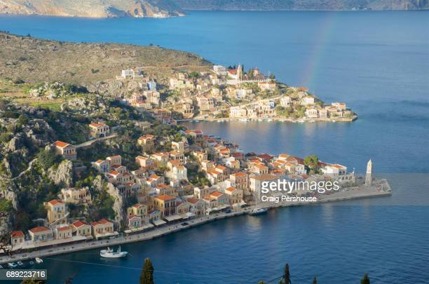 view over symi harbour, kokkinohama bay and houses of gialos (yialos), with rainbow above. - symi stock photos and pictures