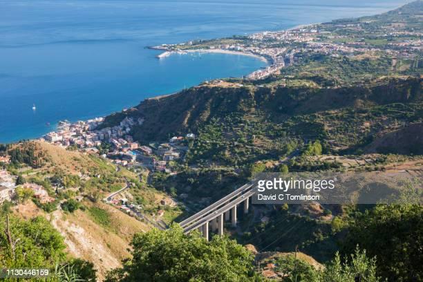 view over the bay of naxos to distant giardini-naxos, motorway prominent, castelmola, taormina, messina, sicily, italy - naxos sicily stock pictures, royalty-free photos & images