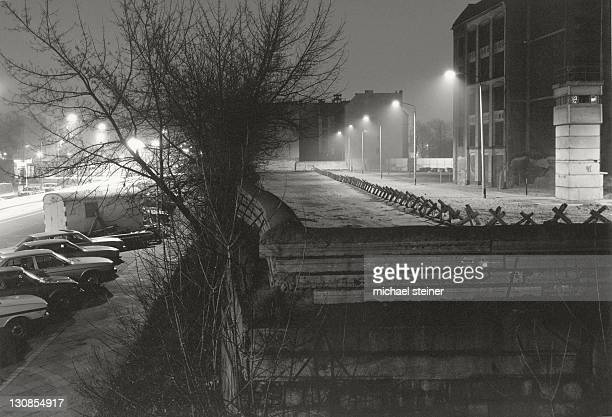 View over the Berlin Wall in 1985, illuminated inner German border, known as the Death Strip, with a guard tower and an uninhabited apartment block in the eastern part of Berlin, Berlin, Germany, Europe