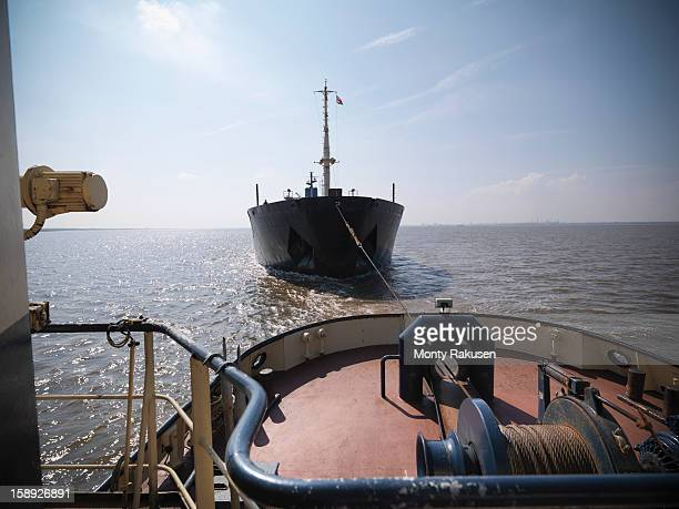 View over the bow of tugboat towing ship at sea