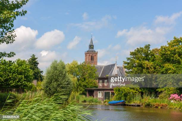 view over the canal towards the church of graft de rijp - north holland stock pictures, royalty-free photos & images