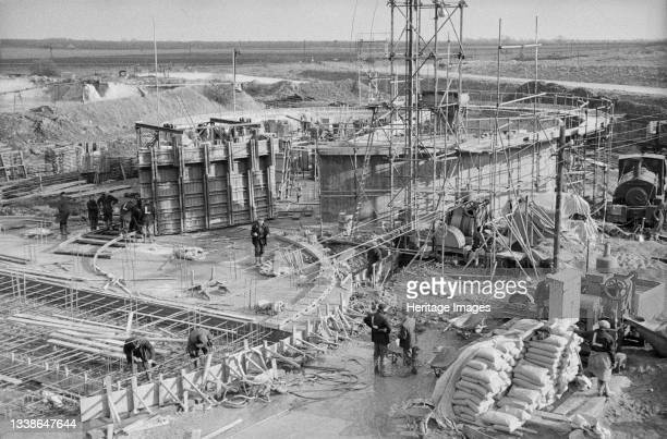 View over the construction site for two sugar silos at Bardney Sugar Factory, showing Laing workers carrying out various tasks. Two sugar silos were...