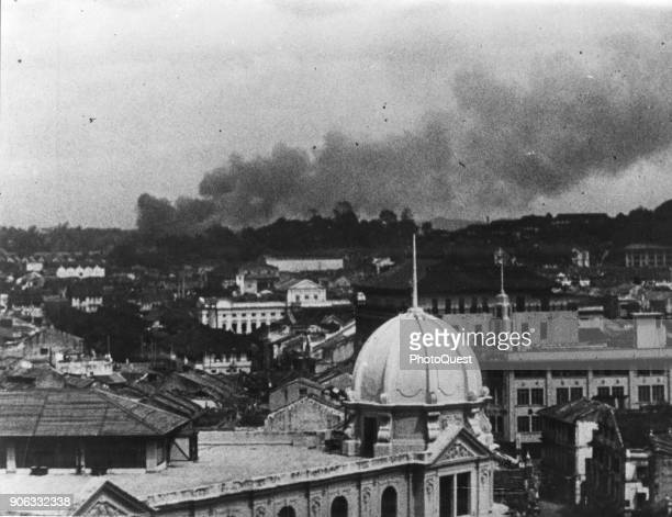 View over the dome of the Chartered Bank of India Australia and China of smoke from bombs and artillery fire during conflict shortly before the...