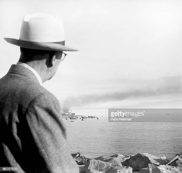 View over the shoulder of a man who stands on a rocky beach and watches a large cardo ship in the bay, Valparaiso, Valparaiso Region, Chile, November...