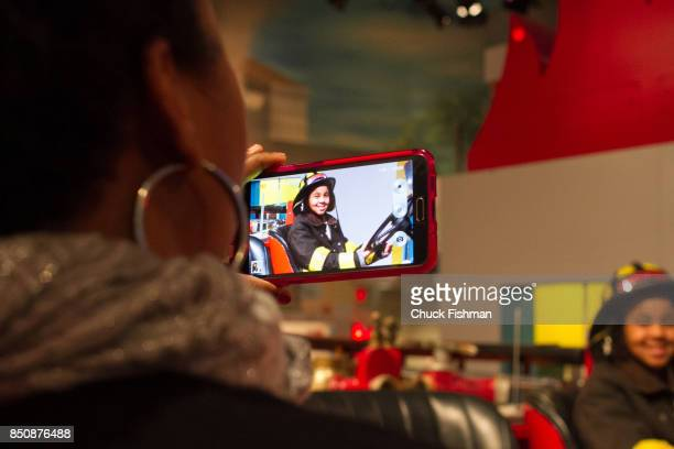 View over the shoulder of a woman as she uses a smartphone to photograph a young boy dressed as a firefighter at the Cradle of Aviation Museum Garden...