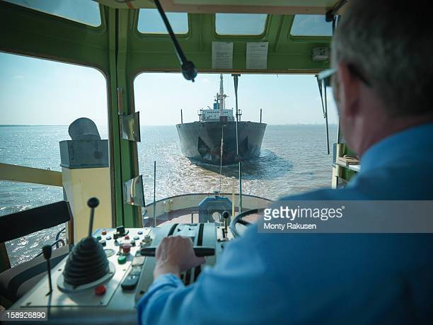 View over the shoulder of captain at the  bridge of tugboat towing ship at sea