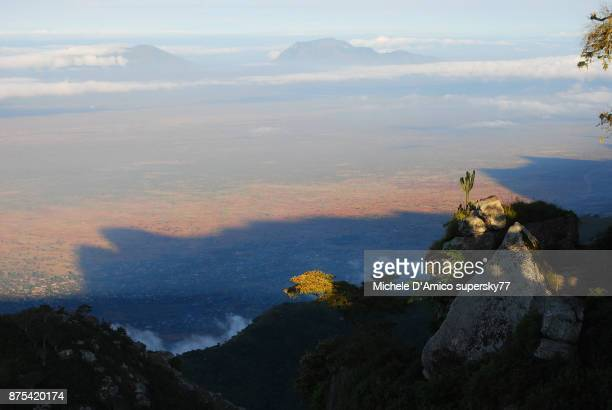 view over the wide red expanses of the masai steppe - mount meru stock photos and pictures