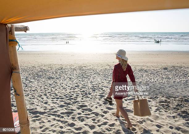 view past beach canopy to woman carrying beach bag - woman carrying tote bag stock photos and pictures