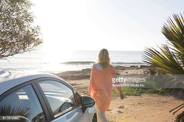 View past car door as woman walks across beach