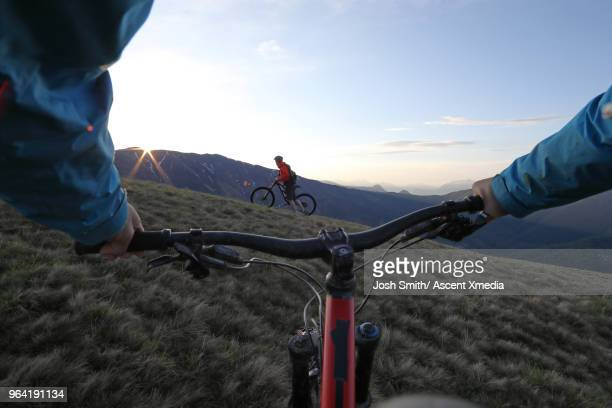 View past handlebars to mountain biker and distant mountains