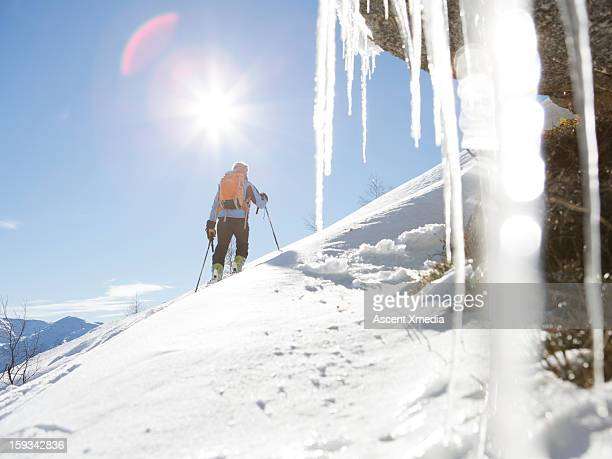 View past icicles to skier ascending slope