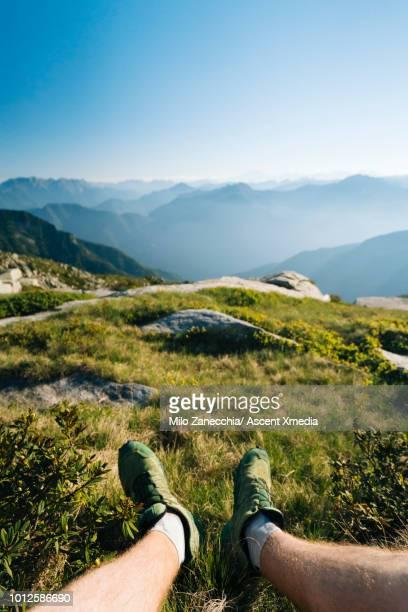 view past legs of male trail runner to alpine meadow - unterer teil stock-fotos und bilder