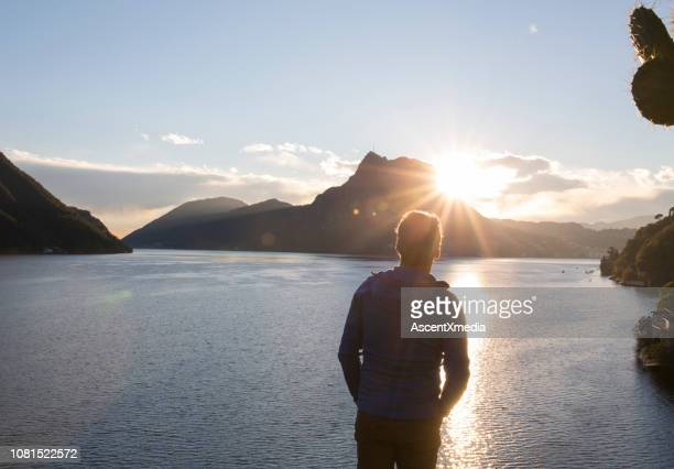 view past man to lake, sun and mountains - back lit stock pictures, royalty-free photos & images
