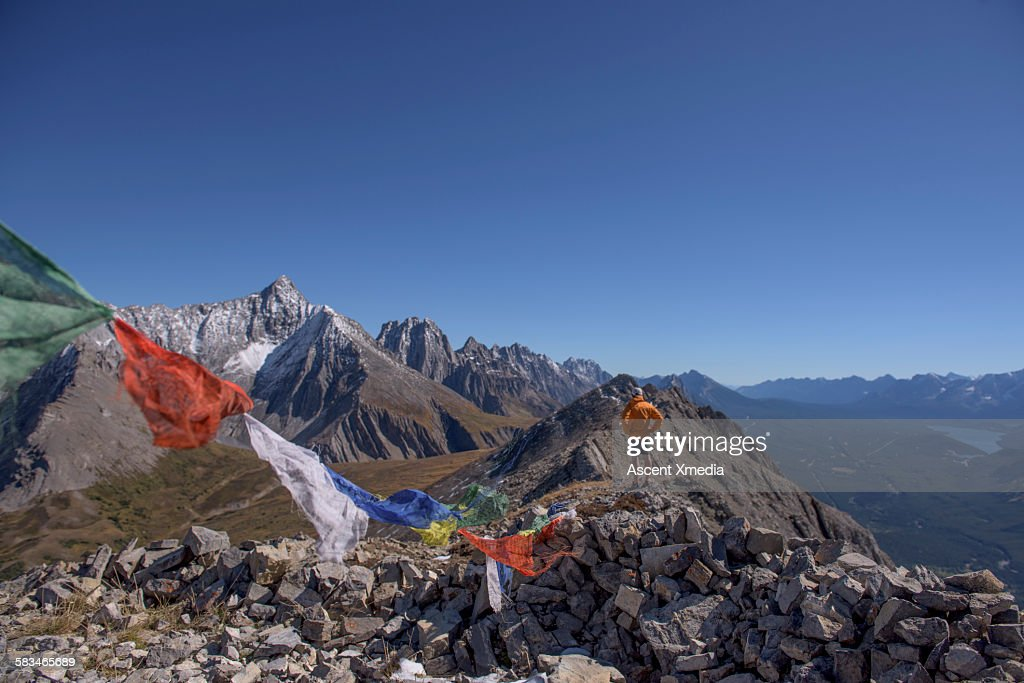 View past prayer flags to man on mountain summit : Stock Photo
