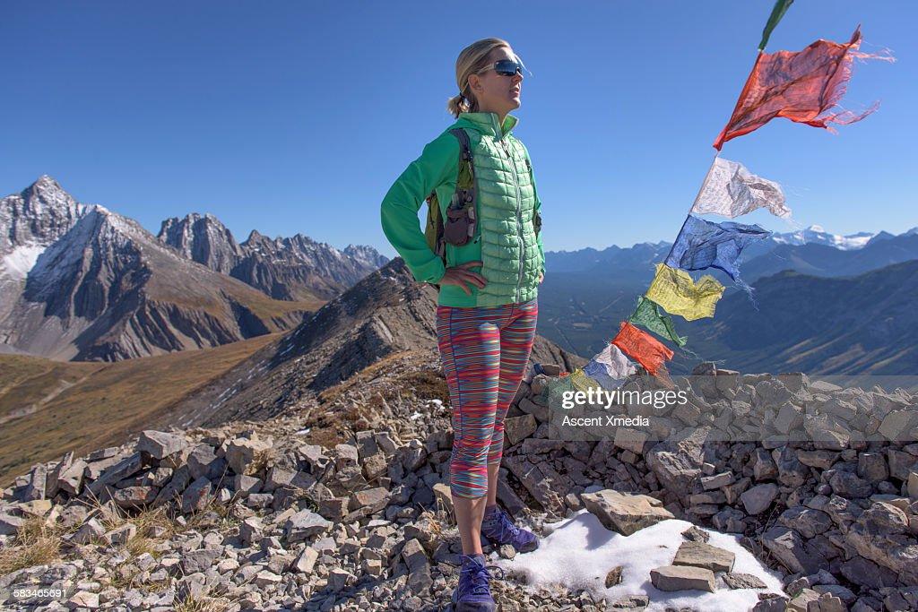 View past prayer flags to woman on mountain summit : Stock Photo
