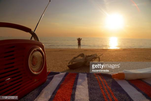 view past radio, book and sandals to woman on beach - radio stock pictures, royalty-free photos & images