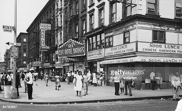 View pedestrian traffic on the northeast corner od the intersection of West 125th Street and Lenox Avenue in Harlem New York New York July 2 1963