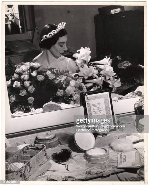 View, reflected in a mirror, of English ballet dancer Alicia Markova backstage in her dressing room, surrounded by flowers, New York, New York, 1950s.