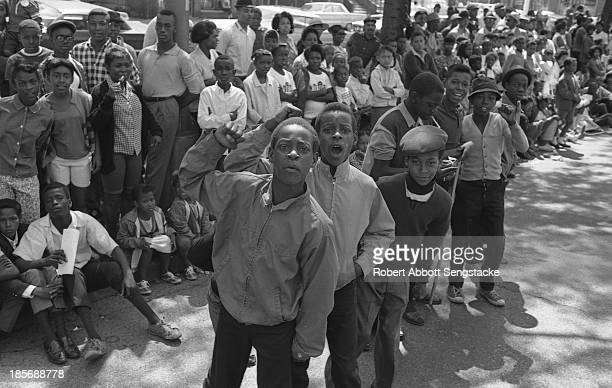 View showing the crowds lined up along the street to watch the Bud Billiken Day parade, Chicago, Illinois, mid to late 1960s .