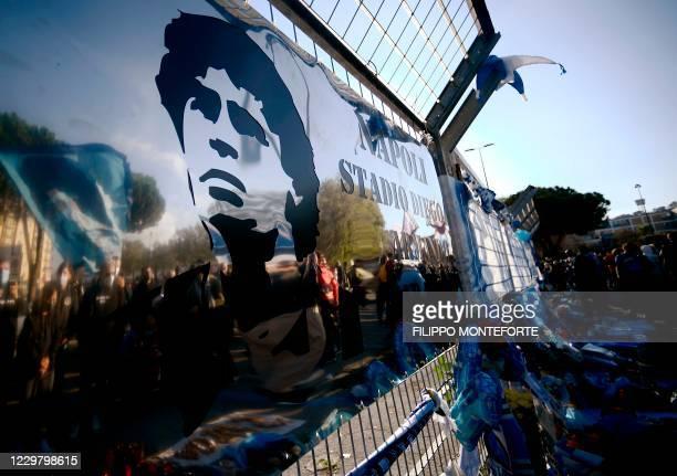 "View shows a board rechristening the stadium to ""Diego Armando Maradona stadium"", as people gather on November 26, 2020 outside the San Paolo stadium..."