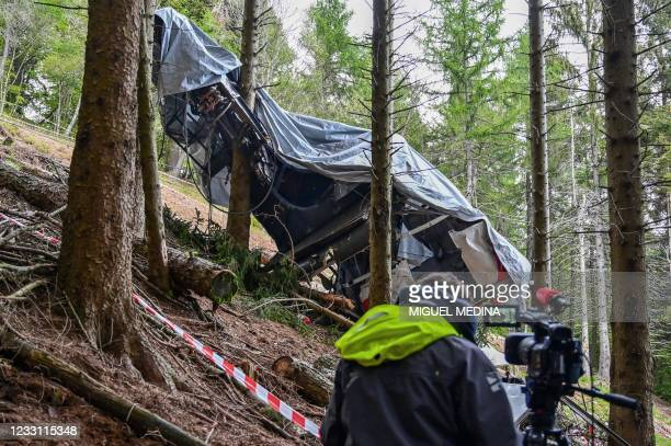 View shows a journalist working by the cabin's wreckage covered with a tarpaulin on May 26, 2021 on the slopes of the Mottarone peak above Stresa,...