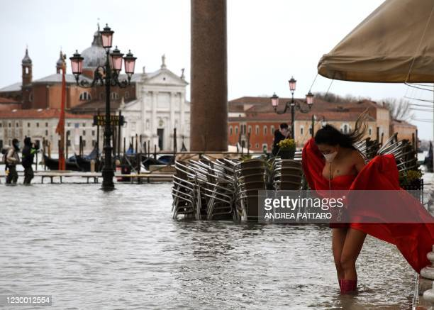 """View shows a model holding her dress on a flooded St. Mark's Square on December 8, 2020 following a high tide """"Alta Acqua"""" event following heavy..."""