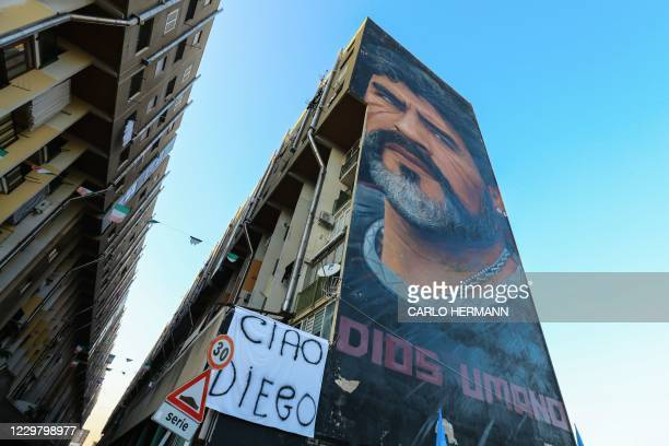 """View shows a mural of late Argentinian football legend Diego Maradona, with the inscription in Spanish """"Dios Umano"""" on November 26, 2020 in Naples,..."""