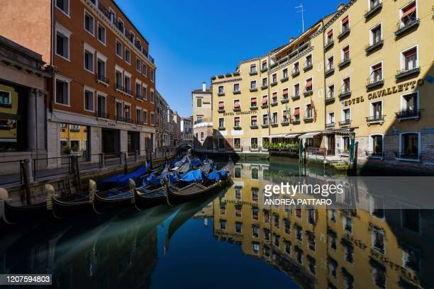 View shows clear waters by gondolas in a Venice canal by Hotel Cavalletto on March 18, 2020 as a result of the stoppage of motorboat traffic,...