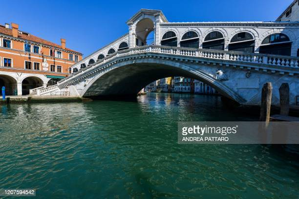 View shows clear waters in Venice's Grand Canal at the Rialto Bridge on March 18, 2020 as a result of the stoppage of motorboat traffic, following...