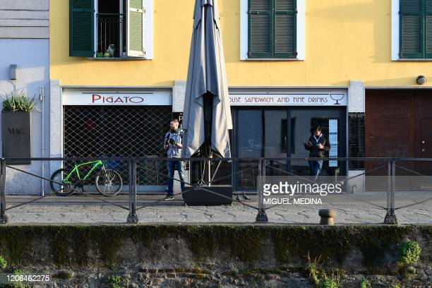 A view shows people relaxing along a canal as the sun sets over the Navigli district of Milan on March 10 2020 as Italy imposed unprecedented...