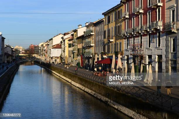 A view shows people strolling along a canal as the sun sets over the Navigli district of Milan on March 10 2020 as Italy imposed unprecedented...