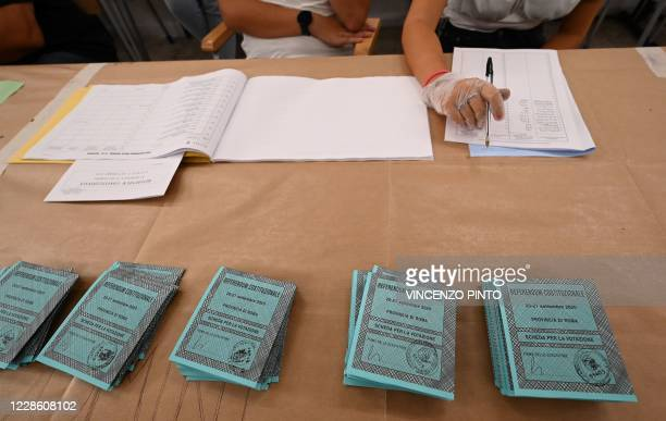 View shows referendum ballot papers and voting officers, one wearing gloves, at a polling station in downtown Rome on September 20, 2020. - Italians...