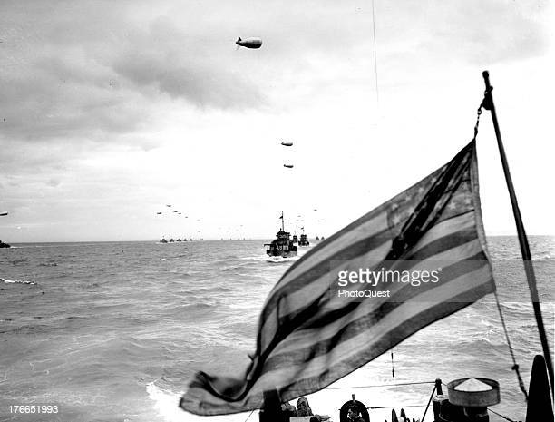 View somewhere in the English Channel of columns of Coast Guard LCIs protected by barrage balloons against low flying Nazi strafers as they advance...