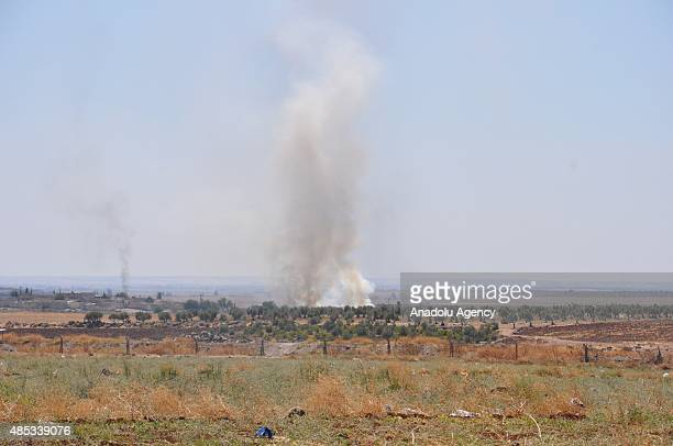 A view taken from Kilis province Turkey shows that smoke rises on August 27 2015 during the clashes between Free Syrian Army and Daesh in Syria's...