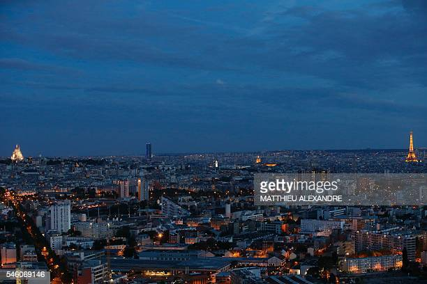 A view taken from SaintDenis Paris northern suburb on July 10 2016 shows Paris by night with the Eiffel tower the Montparnasse tower and the Sacre...