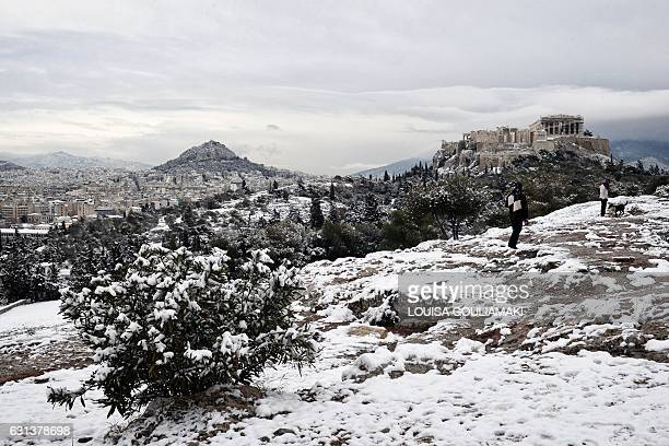 A view taken from the Pnyx hill in Athens shows the snowcovered Acropolis after a rare heavy snowfall on the city on January 10 2017 A cold snap...