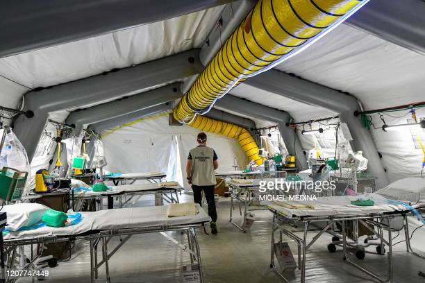 A view taken on March 20 2020 in Cremona southeast of Milan shows a worker checking equipment in a patients' tent at a newly operative field hospital...