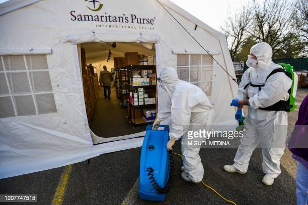 A view taken on March 20 2020 in Cremona southeast of Milan shows cleaning personnel in protective gear prparing to enter to spray disinfectant in...